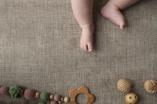 Flatlay avec de minuscules jambes de bébé nouveau-né potelées et des jouets faits à la main en tricot et en bois.
