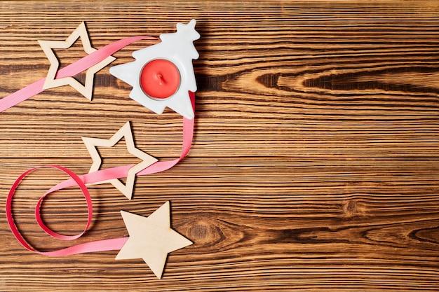 Flatlay de noël avec des étoiles de bougie d'arbre de noël et ruban rose sur fond de bois
