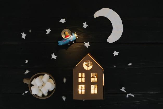 Flatlay de noël avec des étoiles de lune en papier et une maison sur la vue de dessus de fond en bois