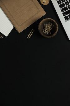 Flatlay d'ordinateur portable, feuille de cahier d'artisanat, clips dans un bol en bois sur fond noir