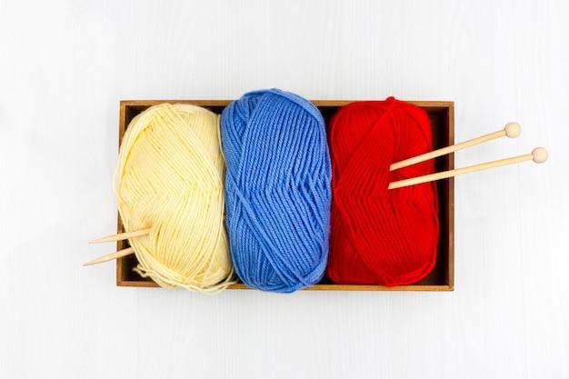 Flatlay de pastilles multicolores tricotant des écheveaux de laine et des aiguilles à tricoter sur fond blanc