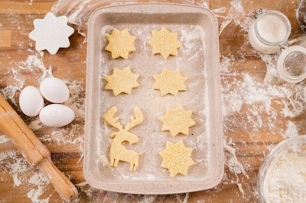 Flatlay de plateau avec deux rangées de biscuits crus entourés d'oeufs, rouleau à pâtisserie, farine, emporte-pièces et pot ouvert de sucre