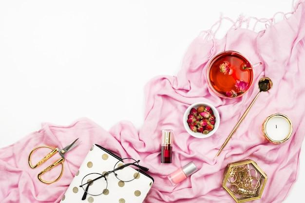 Flatlay de style de vie féminin avec foulard rose, thé d'hibiscus, bougies, agenda et autres accessoires sur blanc