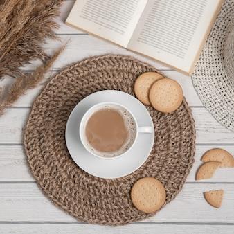 Flatlay avec tasse de cookies de tapis de jute americano ou espresso et livre sur une table en bois blanche.