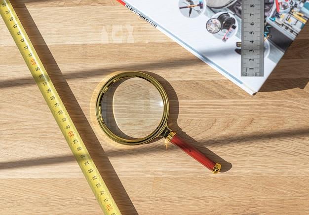 Flatlay technique avec loupe, règle, ruban à mesurer et livre sur un bureau en bois, vue de dessus. concept d'étude technique.