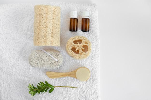 Flatley de beauté pour les soins personnels. luffa, bouteilles en verre, pierre ponce, luffa, lavage du visage, peigne sur une serviette blanche