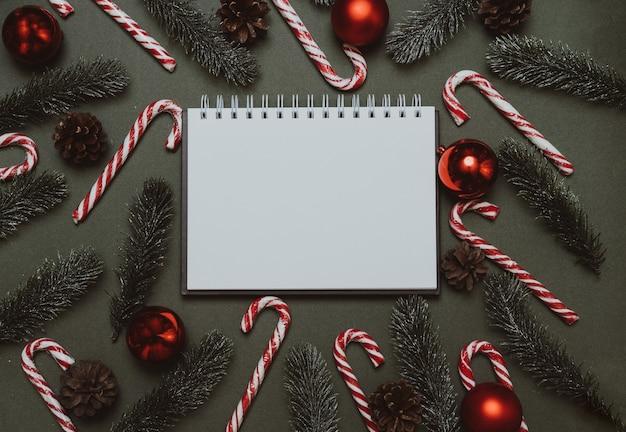 Flatley du nouvel an. branches de sapin de noël, cônes, boules et roseaux caramel sur fond vert uni. espace vide pour votre annonce ou texte.