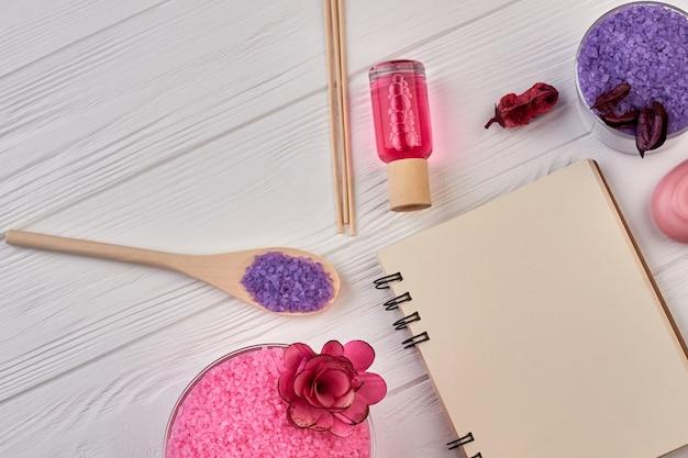 Flay lay arrangement de trucs de soins du corps spa. bloc-notes de banque vue de dessus avec sel coloré et lotion.
