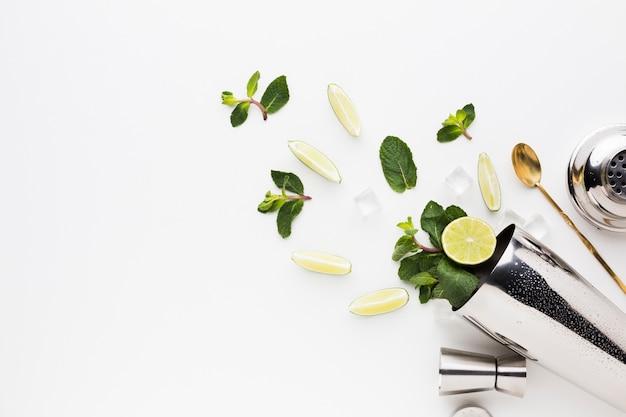 Flay lay de l'essentiel du cocktail avec des tranches de citron vert et de la menthe