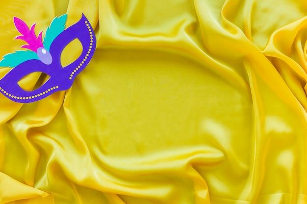 Flay lay de masque de carnaval sur tissu jaune avec copie espace