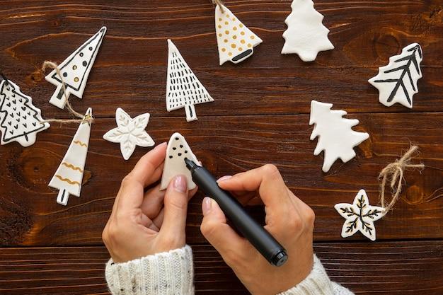 Flay lay of hands dessin sur des décorations pour arbres de noël