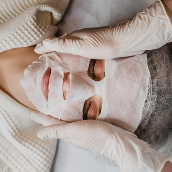 Flay lay of young woman getting a skin mask treatment