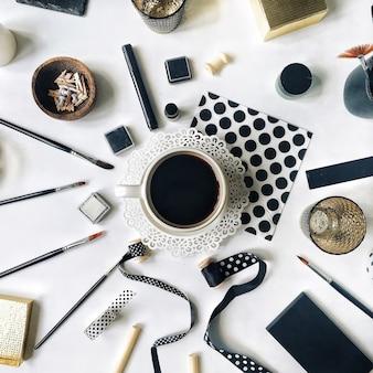 Flay lay workspace home office avec tasse de café noir, carnet de croquis, serviettes, rubans, pinceaux sur blanc