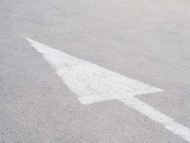Flèche blanche sur asphalte