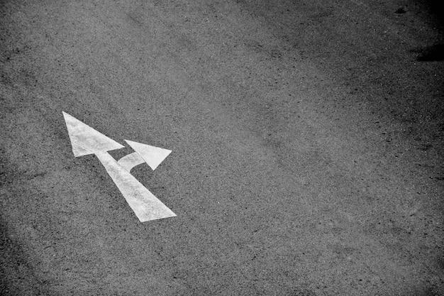 Flèche blanche peinte sur une route goudronnée