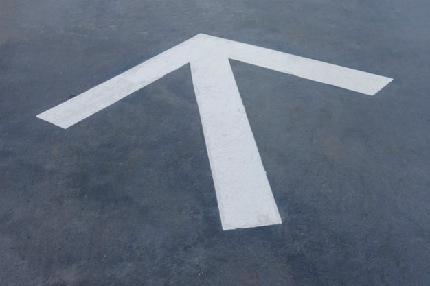 Flèche blanche pointue sur fond d'asphalte