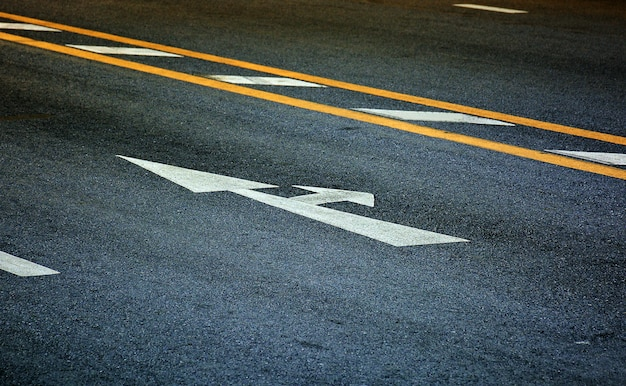 Flèche blanche et tournez à droite sur l'asphalte noir