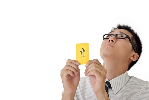 Flèche en carton jaune indiquant la direction de la tenue par l'homme d'affaires