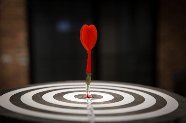 Flèche de cible de fléchette rouge frappant sur bullseye