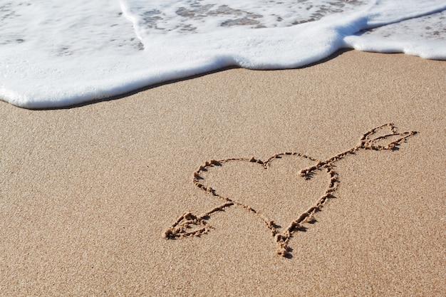 Flèche de cupidon au cœur dans le sable.