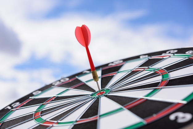 Flèche de dart rouge frapper dans le centre de la cible de fléchettes avec fond de ciel bleu