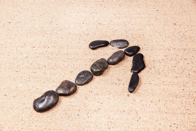 Flèche dessinée avec des galets sur le sable de la plage