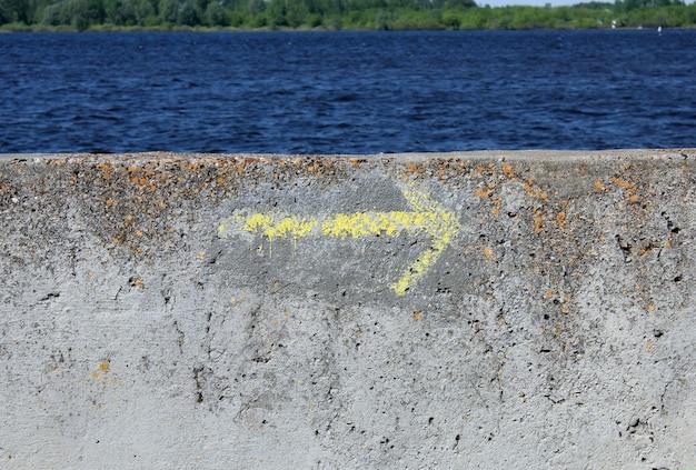 Flèche de direction droite peinte en jaune sur le remblai de la rivière