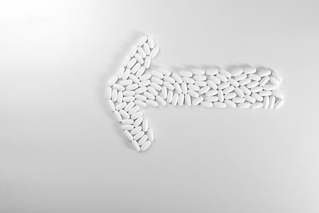 Flèche de direction faite avec des pilules isolé sur fond blanc, concept de médecine