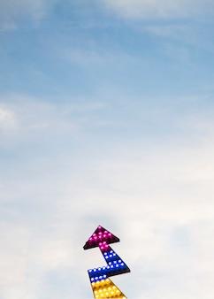 Flèche directionnelle illuminée dans le ciel