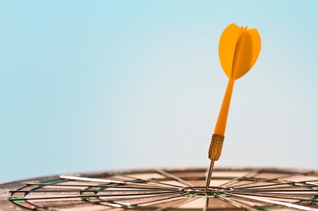 Flèche de fléchette orange frapper le point de mire dans la cible centrale du jeu de fléchettes sur fond de ciel bleu avec espace de copie