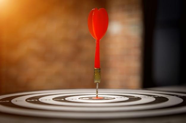 Flèche de fléchette rouge frappant dans le centre cible du jeu de fléchettes sur bullseye avec la lumière du soleil