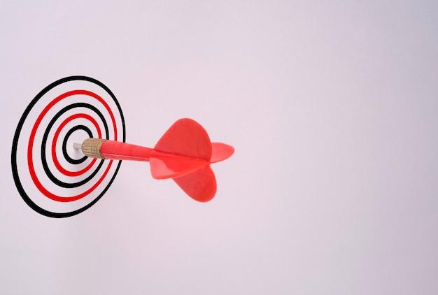 Flèche de fléchette rouge a frappé sur le plateau cible et fond blanc, concept de cible objectif de réussite commerciale.