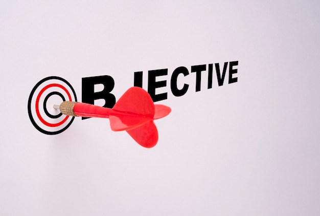 Flèche de fléchette rouge frappé sur le plateau cible isolé sur blanc