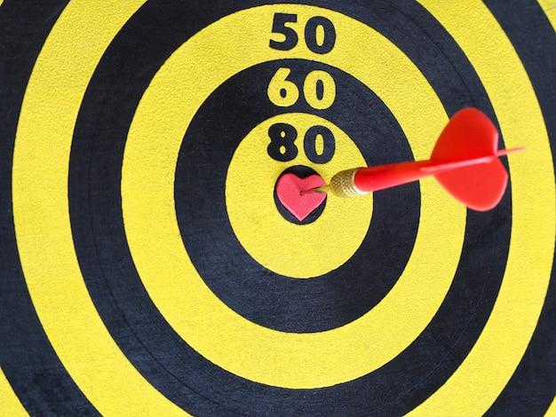 Une flèche fléchette rouge frapper sur le coeur en forme au centre de la cible