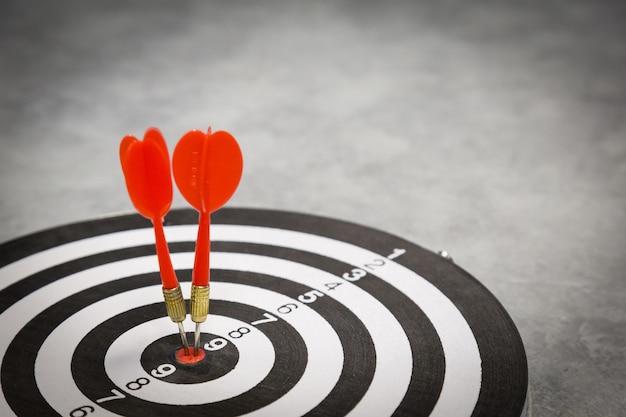 Flèche de fléchette rouge frapper dans le centre cible du jeu de fléchettes sur bullseye avec style vintage lumière du soleil.