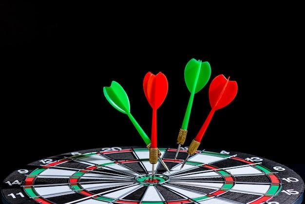 Flèche de fléchette rouge et verte frappant le centre cible dart board isolé, définition du concept de réalisation de l'objectif objectif ambitieux et prêt à atteindre l'objectif