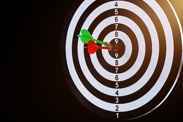 Flèche fléchette rouge et verte frappant le centre cible est un jeu de fléchettes isolé sur une surface noire