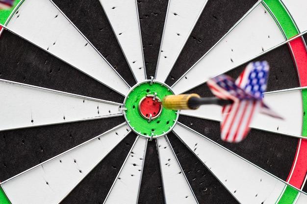 Flèche de fléchettes frappant au centre cible du jeu de fléchettes