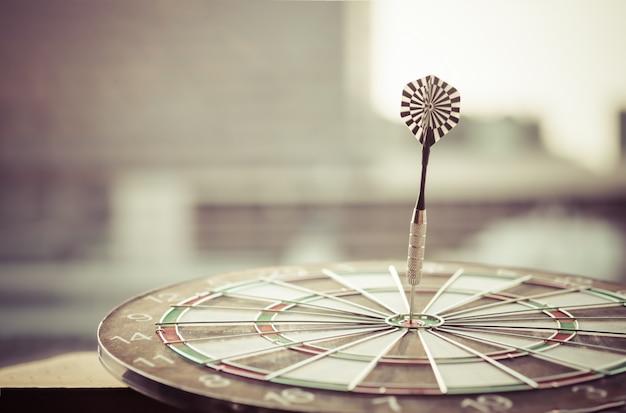 Flèche de fléchettes frapper dans le centre cible du jeu de fléchettes avec fond de ville et de coucher de soleil moderne.