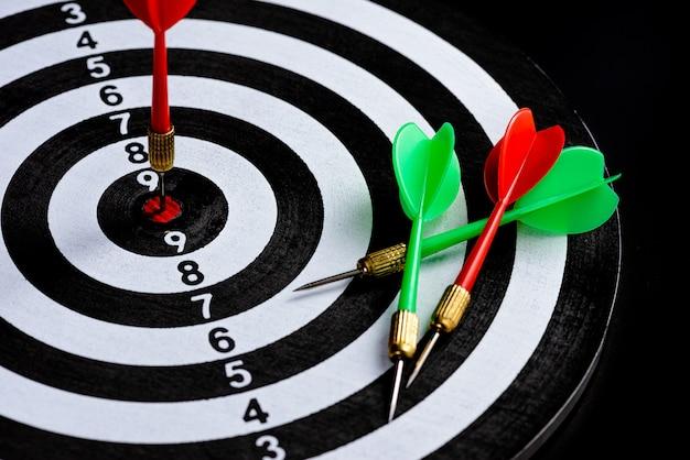 Flèche de fléchettes rouge et vert frappant le centre de la cible dart board isolé sur fond noir,