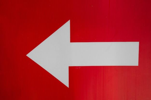 Flèche gauche blanche sur fond rouge
