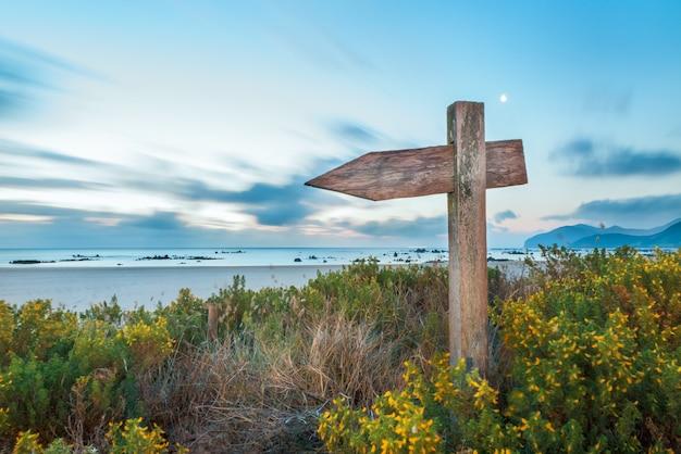 Flèche indicatrice en bois dans les dunes de la plage