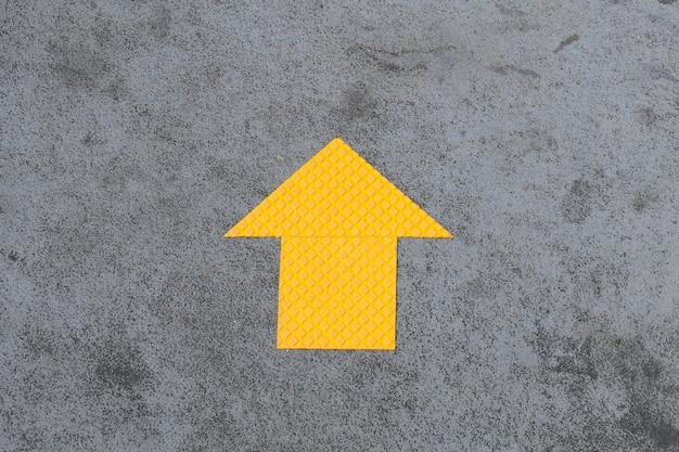 Flèche jaune peinte dans un mur.