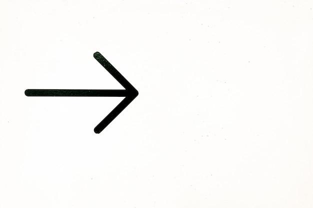 Flèche noire peinte sur le mur blanc indiquant la direction vers la droite, copie espace.
