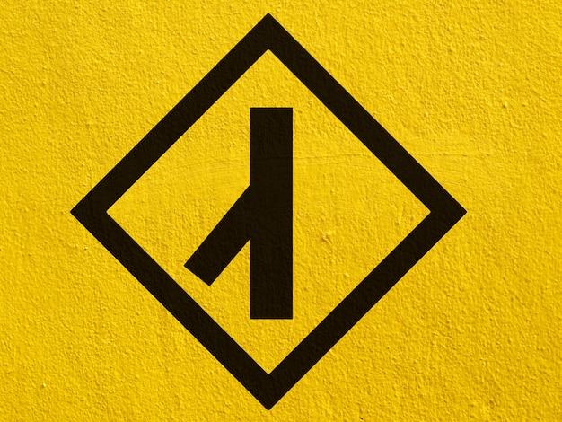 Une flèche noire pointe sur un mur de stuc à l'extérieur