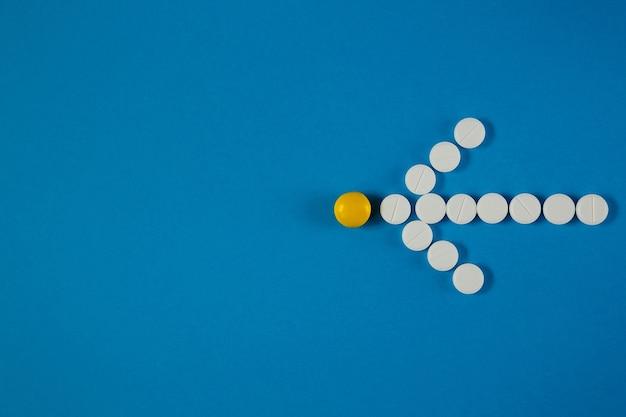 La flèche des pilules blanches indique la pilule jaune d'en haut