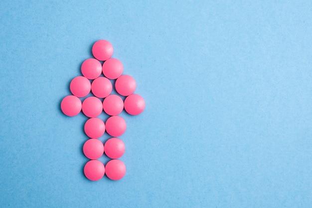 Flèche de pilules roses pointant vers le haut sur un fond bleu.