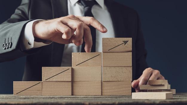 Flèche pointant vers le haut dessinée sur un escalier fait de chevilles en bois avec un homme d'affaires marchant ses doigts vers le succès.