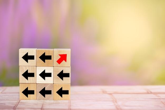 Flèche rouge en bloc de bois pointant dans le sens inverse des flèches noires sur la table en bois. unique, pense différemment et se démarque du concept de la foule