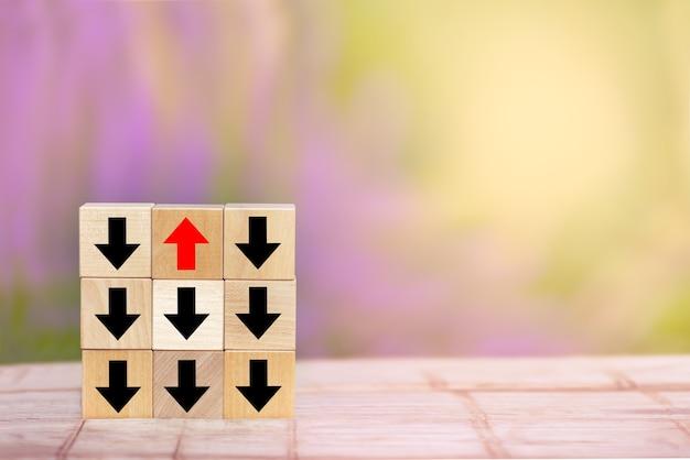 Flèche rouge de bloc de bois pointant dans le sens inverse des flèches noires sur la table en bois.